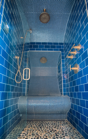 Custom blue subway tile with brass fixtures stand-up/sit down master bath shower.